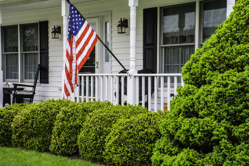 a united states flag on the front porch