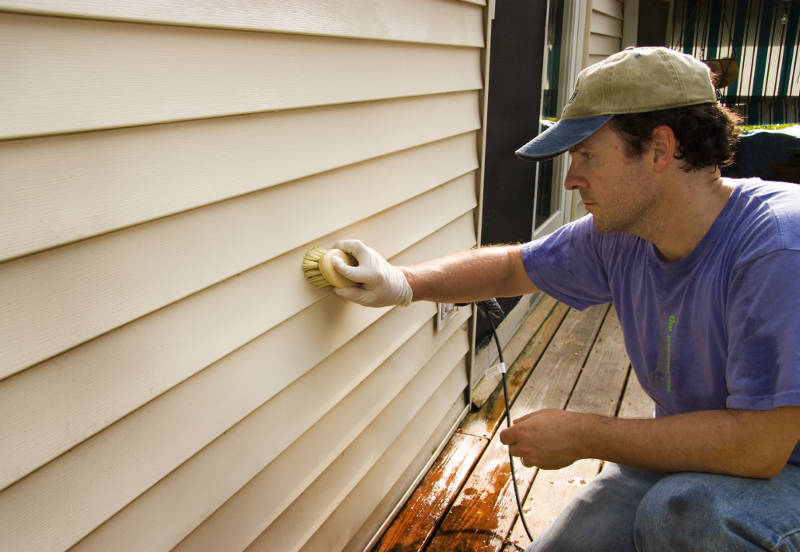 a man cleaning vinyl siding